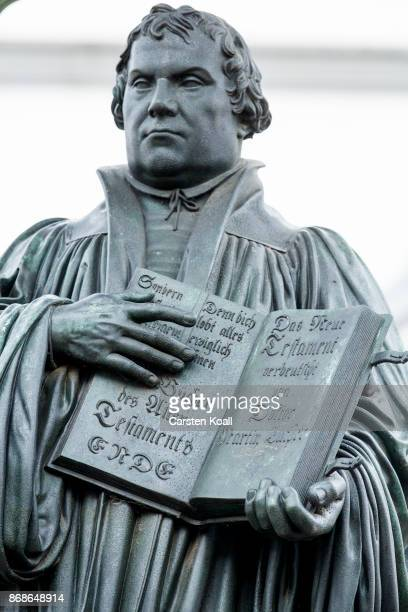Visitors walk in front of a statue of 16thcentury theologian Martin Luther to attend celebrations to commemorate the 500th anniversary of Luther's...