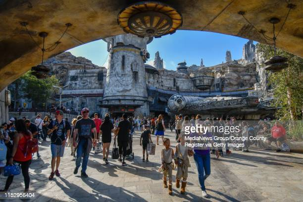 """Visitors walk in front of the Millennium Falcon at Black Spire Outpost on opening day at Star Wars: Galaxy""""u2019s Edge at Disneyland in Anaheim, CA,..."""