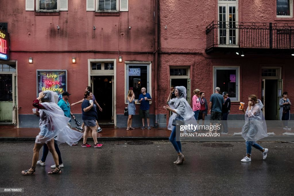 TOPSHOT - Visitors walk in the French Quarter in New Orleans on October 7, 2017. US Gulf Coast residents scrambled with last-minute preparations Saturday as the outer bands of Hurricane Nate began lashing New Orleans amid fears it could intensify into a more powerful Category Two storm. Nate spawned widespread flooding and left dozens of people dead in Central America, the latest in a series of deadly storms to hammer Caribbean islands, Mexico and the southeastern US in this exceptionally busy hurricane season. / AFP PHOTO / Bryan Tarnowski
