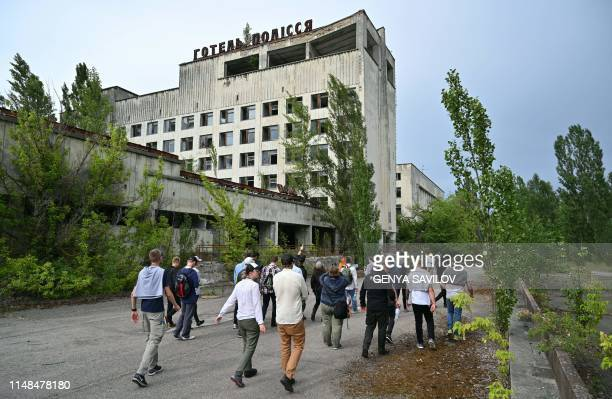 Visitors walk in the ghost city of Pripyat during a tour in the Chernobyl exclusion zone on June 7 2019 HBOs hugely popular television series...