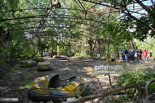 TOPSHOT Visitors walk in the ghost city of Pripyat during a tour in the Chernobyl exclusion zone on June 1 2019 HBOs hugely popular television series...