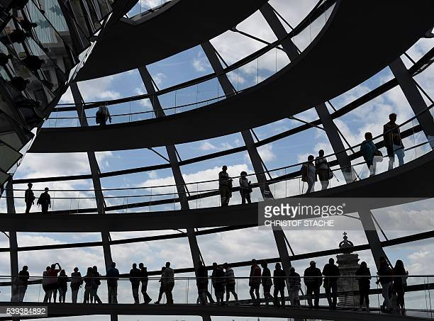 Visitors walk in the glass cupola of the Reichstag building hosting the German parliament in Berlin, Germany, on June 10, 2016. / AFP / CHRISTOF...