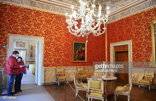 Visitors walk in the LombardyVenetia Throne Room of the Imperial apartments of the Royal Palace on December 3 2012 at the Correr museum in VeniceThe...