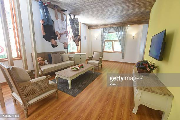 Visitors walk in the villa standing upside down at Yantou village on June 14 2016 in Ningbo Zhejiang Province of China The upsidedown villa covered...