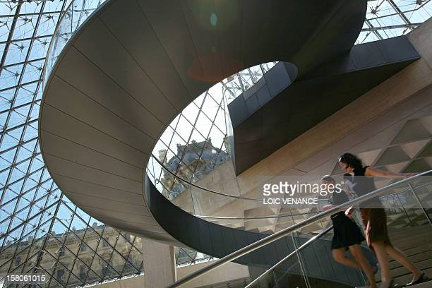 Visitors walk inside the Pyramid, the entrance of the Louvre Museum, on June 17, 2009 in Paris. AFP PHOTO LOIC VENANCE