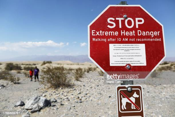 Visitors walk near a sign warning of extreme heat danger on August 17, 2020 in Death Valley National Park, California. The temperature reached 130...