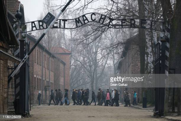 Visitors walk near the notorious Work Makes One Free inscription inside the Auschwitz I memorial concentration camp site on February 15 2019 in...