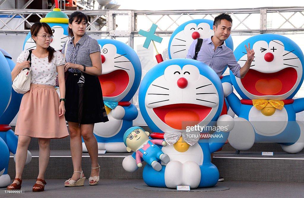 Visitors Walk Next To Japanese Anime Manga Character Doraemon Figures Displayed Celebrate The Characters
