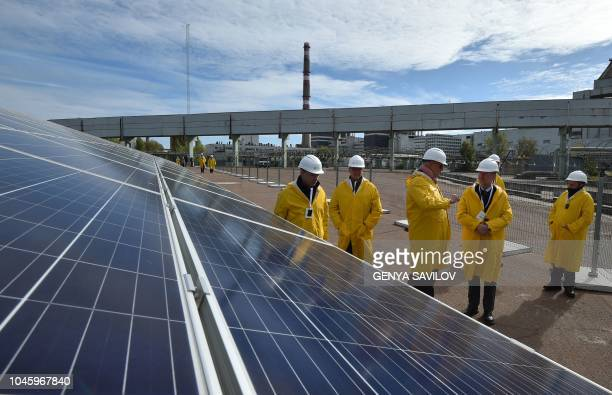Visitors walk next to solar panels during the official opening ceremony of the new onemegawatt power plant next to the New Safe Confinement over the...