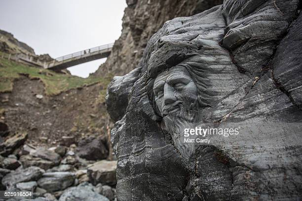 Visitors walk on a bridge above a carving of Merlin at Tintagel Castle in Tintagel on April 28 2016 in Cornwall England The English Heritage managed...