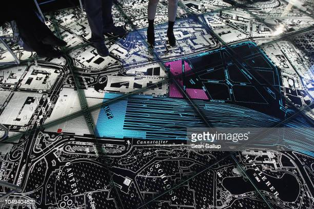 Visitors walk on a floorlit map as part of a presentation highlighting the benefits of the Stuttgart 21 train station project in Hauptbahnhof train...