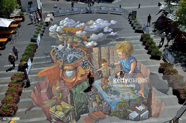 Visitors walk on a giant chalk artwork called 'Wasting Time' at the Chalk Urban Arts Festival in Sydney on October 25 2014 The picture is the biggest...