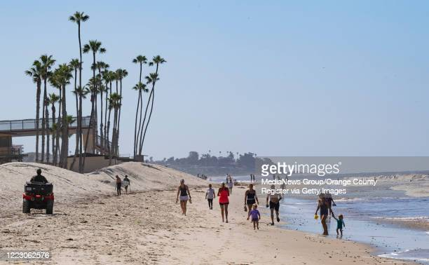 Visitors walk on the beach south of the pier in San Clemente, CA on Tuesday, May 5, 2020. The city opened its beaches for daily active use after...
