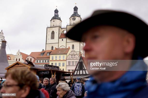 Visitors walk on the Market Place near the Stadtkirche Sankt Marien church during celebrations to commemorate the 500th anniversary of Luther's...