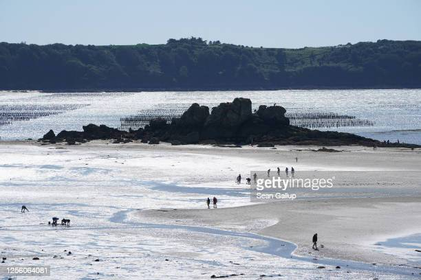 Visitors walk on the mudflats at low tide as an oyster farm is seen in the water behind in Brittany on July 12 2020 at SaintJacutdelaMer France The...