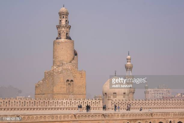 Visitors walk on the roof top of the ninth century mosque of Ibn Tulun in the Egyptian capital Cairo on January 11 with the spiral minaret built in...