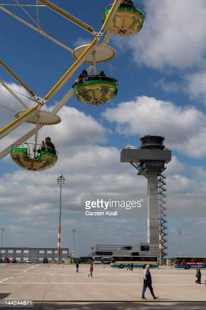Visitors walk on the tarmac below a ferris next to the construction site of the main terminal hall of the new Willy Brandt Berlin Brandenburg...
