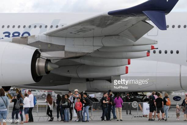 Visitors walk on the tarmac in front of a Airbus A380 on the last day of the International Paris Air Show at Le Bourget Airport near Paris on June 25...