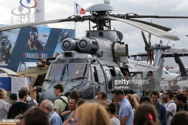 Visitors walk on the tarmac in front of a Caracal military helicopter on the last day of the International Paris Air Show at Le Bourget Airport near...