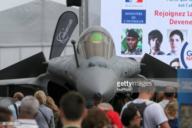 Visitors walk on the tarmac in front of a French Dassault Aviation Rafale jetfighter on the last day of the International Paris Air Show at Le...