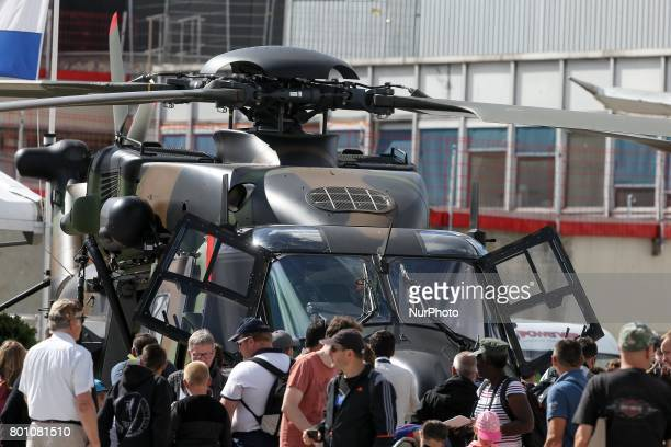 Visitors walk on the tarmac in front of a NH 90 helicopter on the last day of the International Paris Air Show at Le Bourget Airport near Paris on...