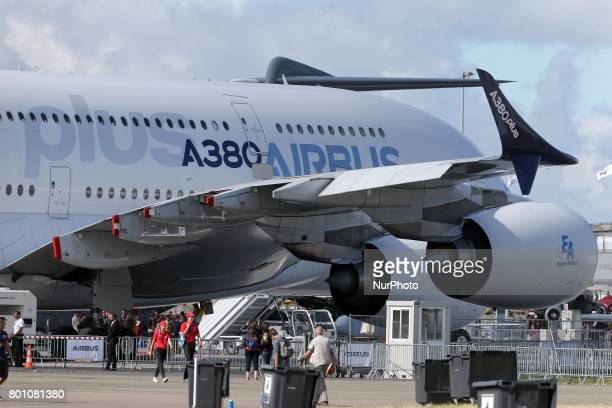Visitors walk on the tarmac in front of an Airbus A380 on the last day of the International Paris Air Show at Le Bourget Airport near Paris on June...
