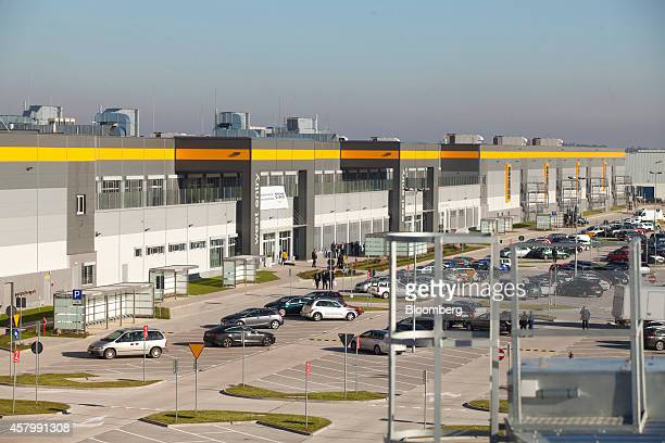 Visitors walk outside the new Amazon Inc fulfilment center on its official day of opening in Bielany Wroclawskie Poland on Tuesday Oct 28 2014 The...