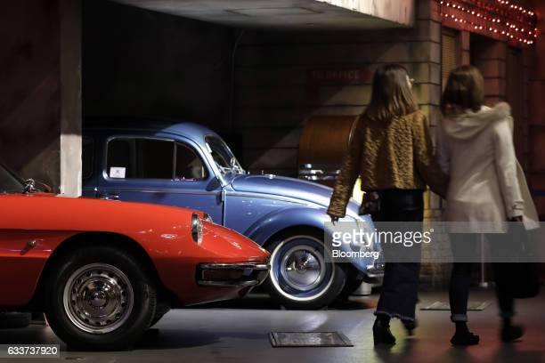 Visitors walk past a 1966 Alfa Romeo Inc 1600 Spider Duet vehicle left and a 1957 Volkswagen AG Beetle Type I vehicle stand on display inside the...