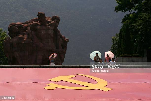 Visitors walk past a billboard featuring the Communist Party of China at the Geleshan Martyrs Cemetery July 1 2006 in Chongqing Municipality China...