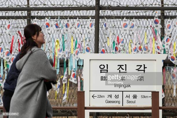 Visitors walk past a fence decorated with South Korean flags and colored ribbons at the Imjingak pavilion near the Demilitarized Zone in Paju South...