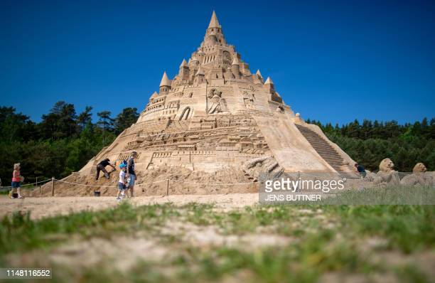 Visitors walk past a giant sand castle that is on display at the sand sculptures festival in Binz on the Baltic Sea island of Ruegen northeastern...