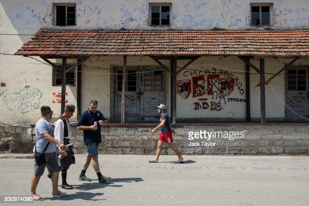 Visitors walk past a graffitied wall in the town during the Guca Trumpet Festival on August 11 2017 in Guca Serbia Thousands of revellers attend the...