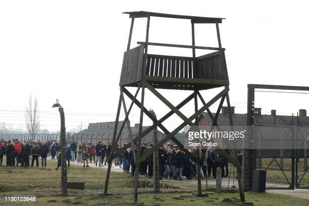 Visitors walk past a guard tower at the Auschwitz IIBirkenau memorial concentration camp site on February 15 2019 in Oswiecim Poland Next year will...
