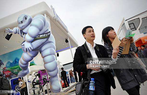 Visitors walk past a large cut out of the mascott of French tyre maker Michelin at the Shanghai Auto Show in Shanghai on April 21 2011 About 2000 car...