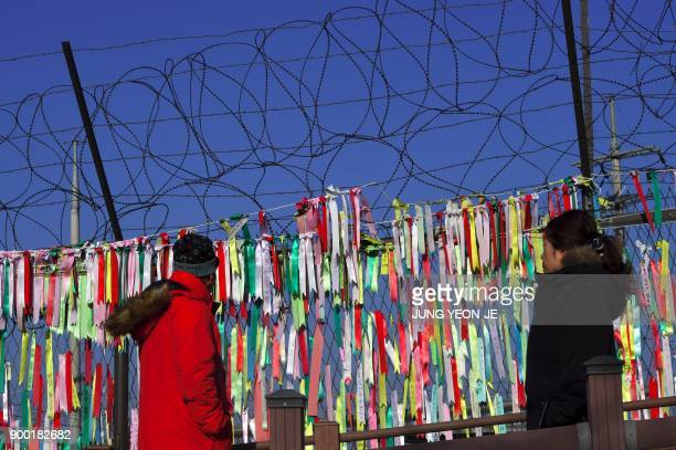 Visitors walk past a military fence covered with ribbons with inscriptions calling for peace and reunification at the Imjingak peace park near the...