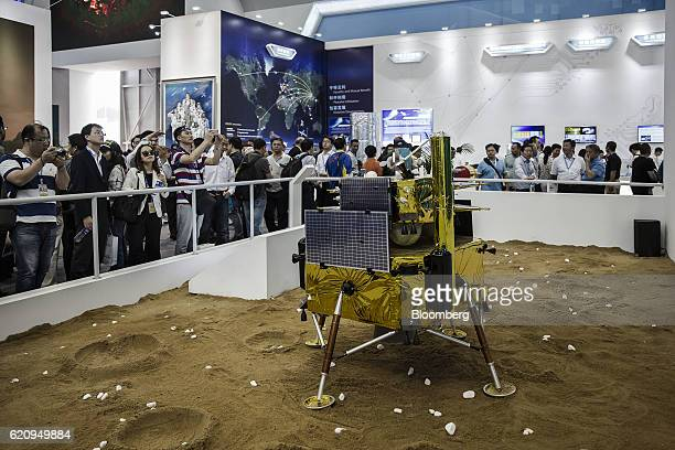 Visitors walk past a model of a Chinese lunar lander at the China International Aviation Aerospace Exhibition in Zhuhai China on Tuesday Nov 1 2016...