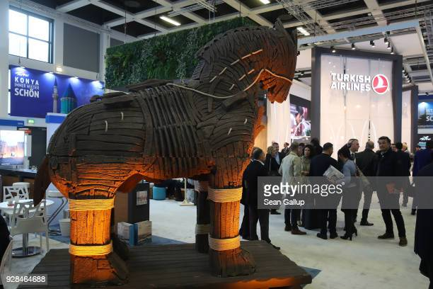 Visitors walk past a model of a Trojan horse in the Turkey hall at the ITB international tourism trade fair on March 7 2018 in Berlin Germany This...