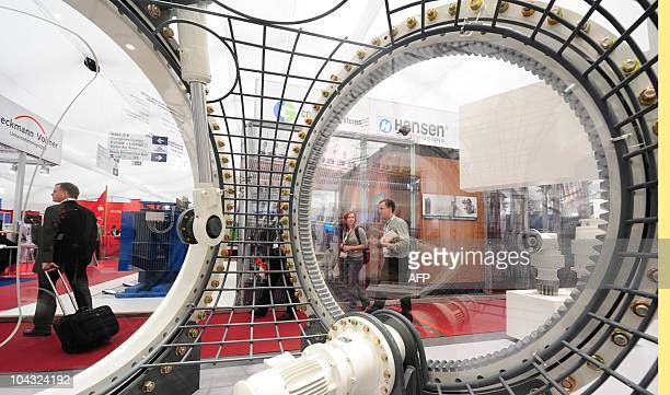 Visitors walk past a model of a wind turbine at the Wind Energy 2010 fair on September 21 2010 in Husum northern Germany The fair for Wind Energy...