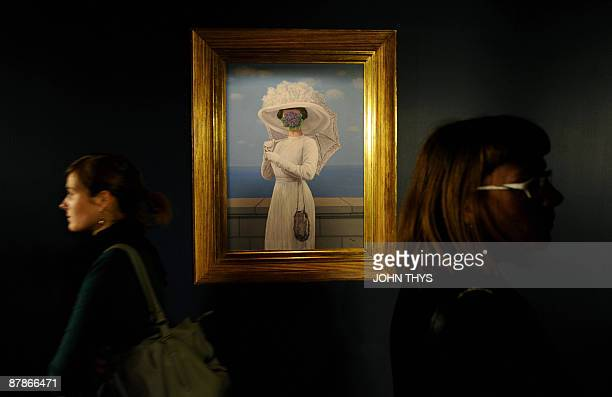 Visitors walk past a painting by the Belgian artiste Rene Magritte at the press opening of the new Margitte museum in Brussels on May 20 2009 The...