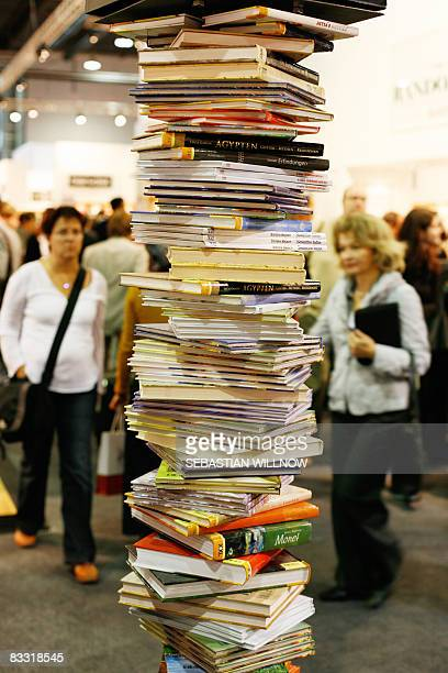 Visitors walk past a pile of books at the Frankfurt Book Fair on October 17 2008 Turkey is guest of honour at the 60th edition of the book fair which...