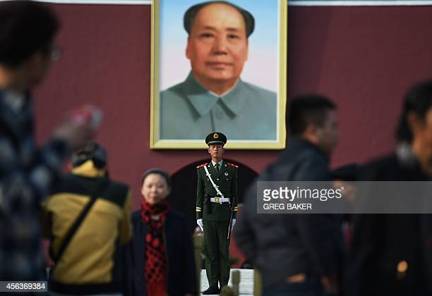 Visitors walk past a portrait of late communist leader Mao Zedong on Tiananmen Gate in Beijing on the eve of National Day on September 30 2014 The...
