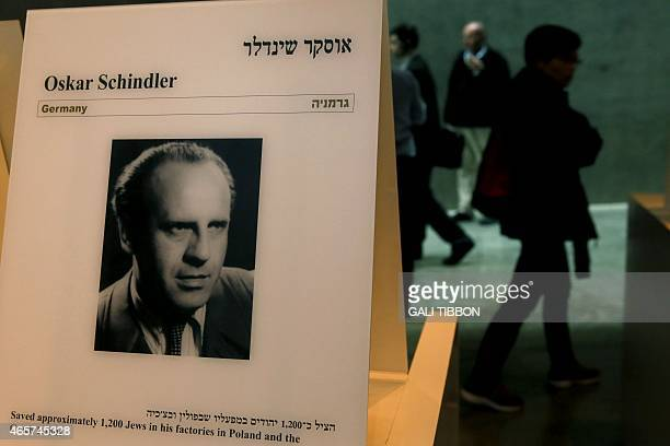 Visitors walk past a portrait of Oskar Schindler at the Yad Vashem Holocaust memorial museum in Jerusalem on March 4 2015 Forty years after his death...