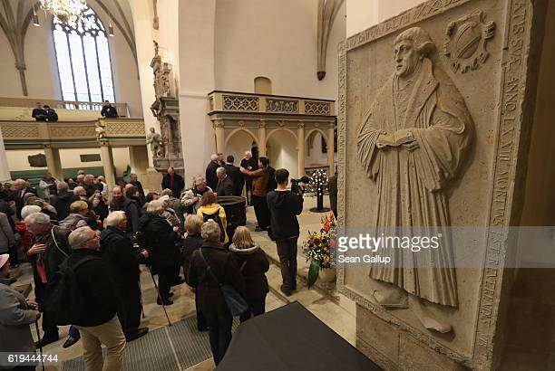 Visitors walk past a sculpted relief that shows theologian Martin Luther on a wall in the Stadtkirche Sankt Marien church following a service to...
