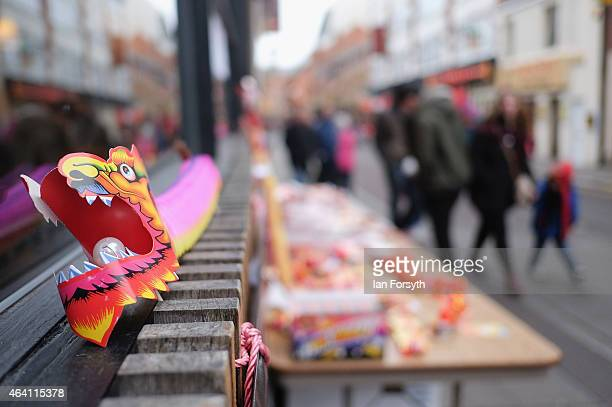 Visitors walk past a stall selling paper dragons as the Chinese community come together to welcome in the Chinese New Year on February 22 2015 in...