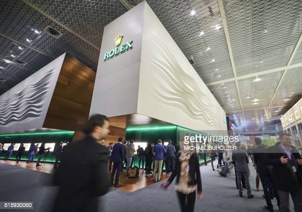 Visitors walk past a stand of Swiss watchmaker Rolex at the watch industry's biggest annual trade fair 'BaselWorld' in Basel on March 16 2016 / AFP /...