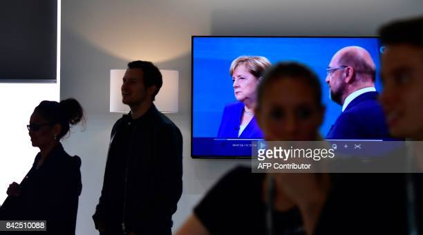 Visitors walk past a television set showing the tvdebate between German Chancellor and leader of the conservative Christian Democratic Union party...