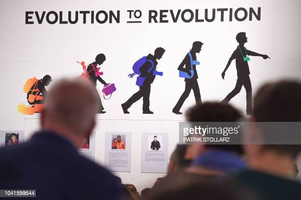 Visitors walk past an advertising at the FujiFilm stand at the Photokina trade fair in Cologne, western Germany on September 27, 2018. - The fair for...
