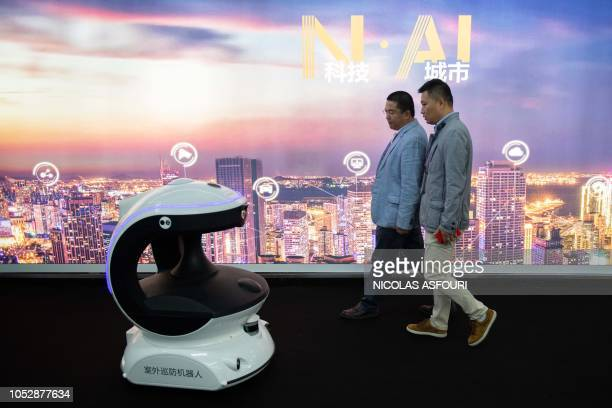 Visitors walk past an AI security robot named APV3 with a facial recognition system at the 14th China International Exhibition on Public Safety and...