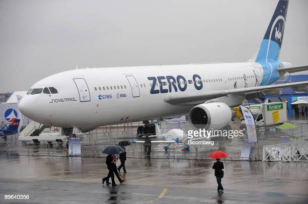Visitors walk past an Airbus A300 ZeroG airplane modified for use as a nearly weightless environment on display at the Paris Air Show in Le Bourget...
