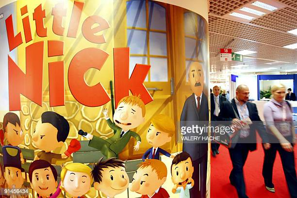 Visitors walk past an animation program poster at the 25th fourday MIPCOM market on October 05 2009 in Cannes southern France Some 12000 TV...